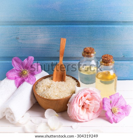 Spa setting. Sea salt in bowl  and towels, aroma oil and flowers on white  wooden background against blue wall. Selective focus. Place for text. Square image.