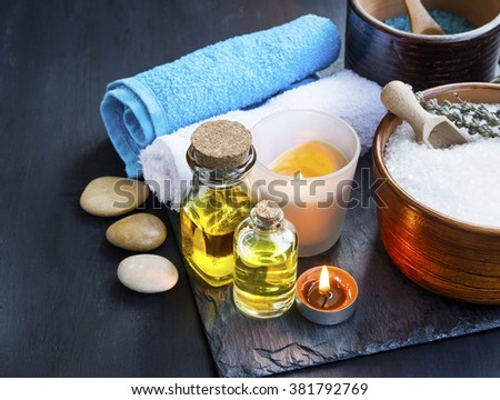 Spa setting still life with body-care oils, towels, candles and spa sea salt