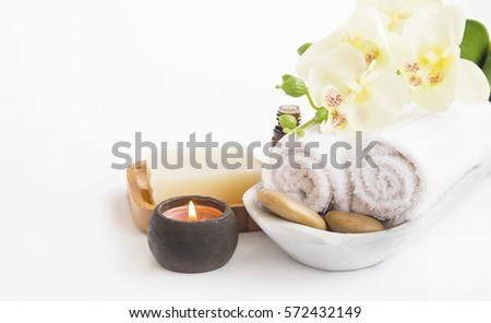 Spa setting still life with orchid flower , candle, soap and towels on white background