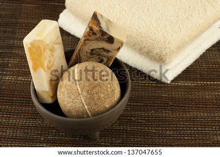 spa setting with bath towels, natural soap and salt