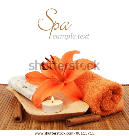 Spa setting with candle, flower, towel, cinnamon and natural soap over white background