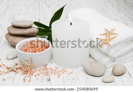 Spa setting with candle, pebble with starfish and towels - stock photo