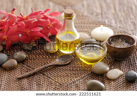 Spa setting with candle ,stone , oil , salt in bowl ,red orchid on mat - stock photo