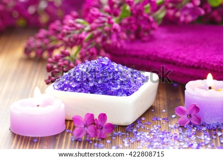 SPA setting with candles, sea salt and lilac flowers - stock photo
