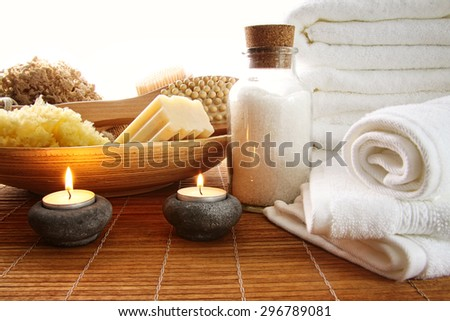 Spa setting with candles, sea salt and towels - stock photo