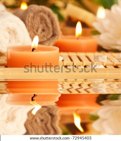 Spa setting with candles, waterlily and pebbles - stock photo