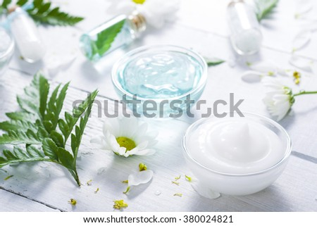 spa setting with cosmetic cream, gel, and fern leaves on white wooden table background