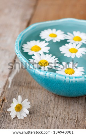 Spa setting with daisies in turquoise bowl - stock photo
