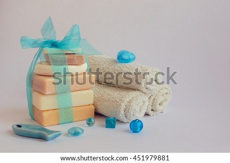 Spa setting with different kind of natural soaps and towels in pastel and blue colors on white background. Bar of natural handmade soap. Tower stack of different soaps on white. Selective focus. - stock photo