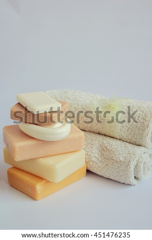 Spa setting with different kind of natural soaps and towels in pastel colors on white background. Tower stack of different handmade soaps on white. Selective focus. Place for text. Copy space. - stock photo