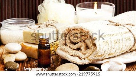 Spa Setting with Essence Oil, Natural Soap, Towel, Sea Salt and Candle - stock photo