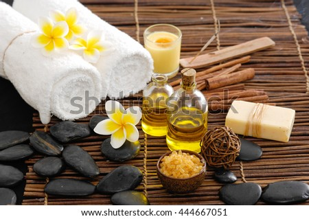 Spa setting with Frangipani with oil ,stones ,towel, soap with mat - stock photo