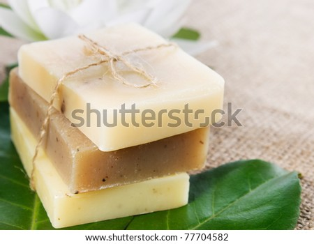 Spa setting with natural soaps and lotus flower. Focus is on the bow. - stock photo