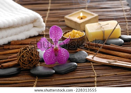 Spa setting with orchid blossom with candle ,stones ,towel, soap with mat