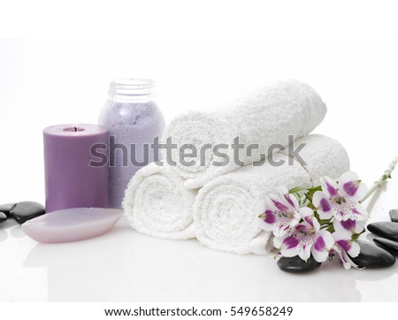 Spa setting with orchid on towel and pile of black stones