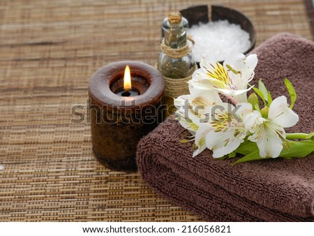 spa setting with orchid on towel on mat