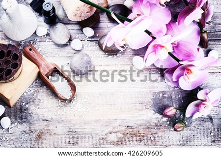 Spa setting with pink orchid, natural soap, herbal massage ball and essential oil. Wellness concept - stock photo