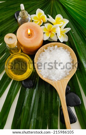 spa setting with salt in spoon and towel,candle,massage oil on palm texture - stock photo