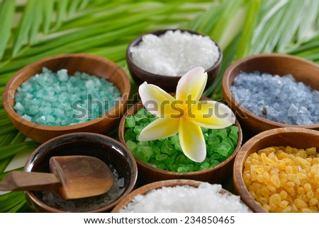 Spa setting with sea salt and colorful perfume in wooden bowl    - stock photo