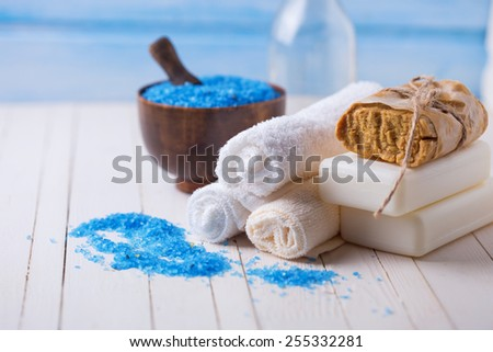 Spa setting with soap, towels, sea salt and aroma oil on  painted wooden boards. Selective focus. - stock photo