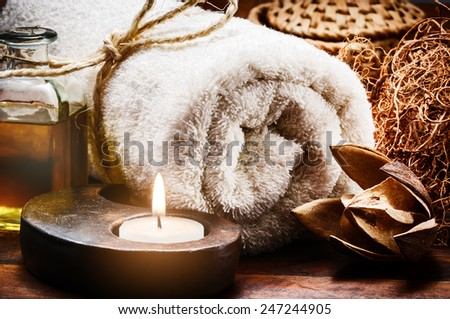 Spa setting with towel and candle in brown tone - stock photo