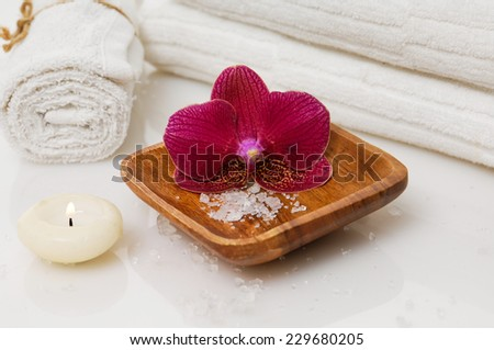 spa setting with towel and red orchid in bowl, candle - stock photo