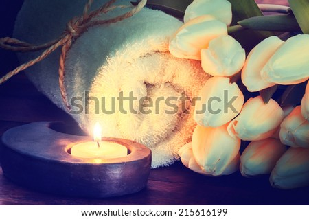 Spa setting with towel, candle and flowers  - stock photo