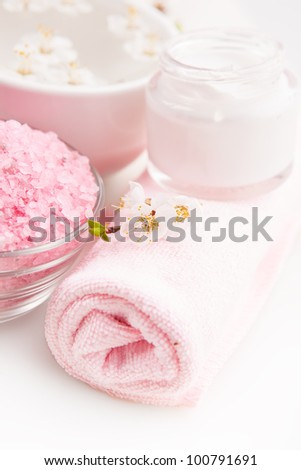 Spa setting with towel, sea salt, water, cream and blossom