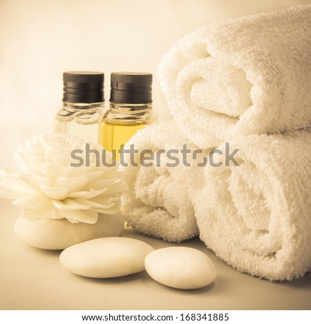 Spa setting with towels aroma oil bottles and hand made flower, warm light in sauna. - stock photo