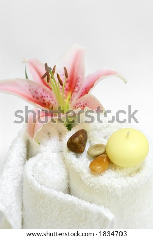 Spa setting with white towels, candles, therapy stones and a lily, on white with copy space - stock photo
