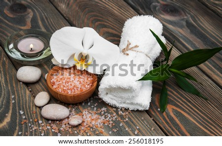 spa still life - a flowers  and towels  on a wooden background - stock photo