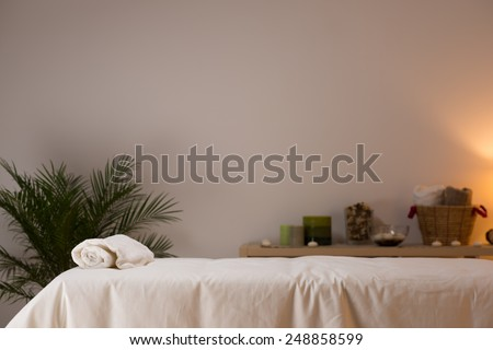 Spa still life at beauty salon interior with aromatic candles and towels - stock photo