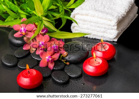 spa still life of blooming twig red orchid flower, phalaenopsis, bamboo with dew, towels and candles on zen basalt stones - stock photo
