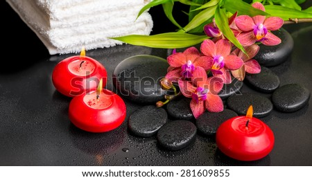 spa still life of blooming twig red orchid flower, phalaenopsis, bamboo with dew, towels and candles on zen basalt stones, panorama  - stock photo