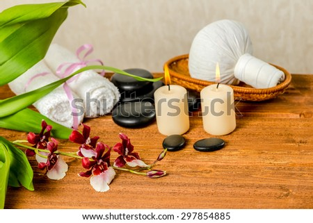 spa still life of orchid flower, Cambria, thai herbal compress balls in basket, towels, zen stones and candles on wooden background, closeup - stock photo