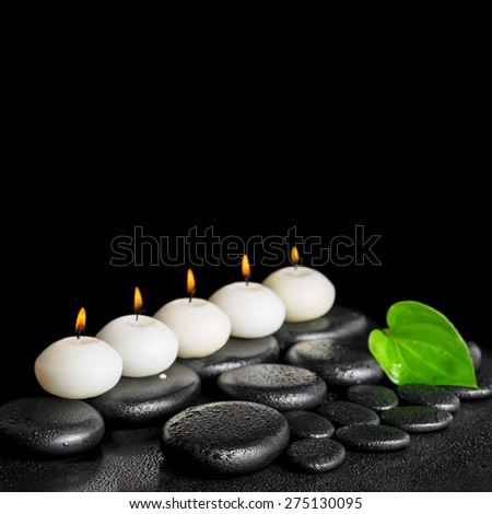 spa still life of row white candles and green leaf on black zen stones background with drops, closeup - stock photo