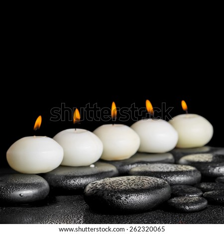 spa still life of row white candles on black zen stones background with dew, closeup  - stock photo