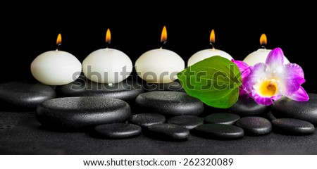 spa still life of row white candles, orchid flower dendrobium and green leaf on black zen stones background with dew, panorama - stock photo