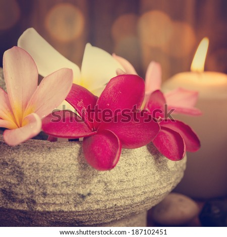 Spa still life setting with aromatic candles, frangipani flower, cold and hot stones in vintage retro style. - stock photo
