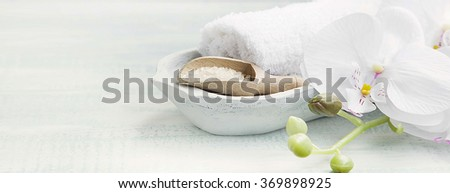 Spa still life setting with white orchid,bath salt and white towels - stock photo