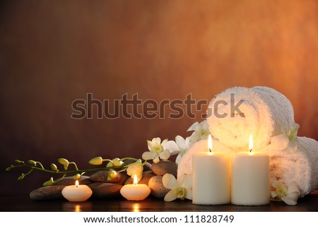 Spa still life with aromatic candles,orchid flower and towel. - stock photo