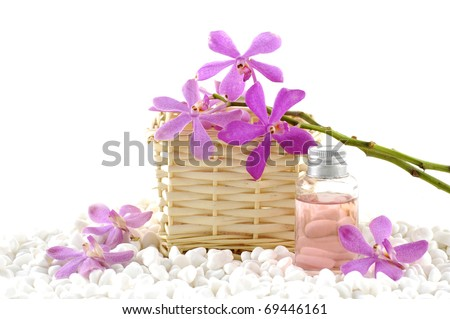 Spa still life with basket of pink orchid and massage oil on zen white pebble - stock photo