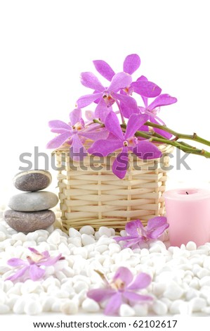 Spa still life with basket of pink orchid with candle and stones on zen white pebble - stock photo