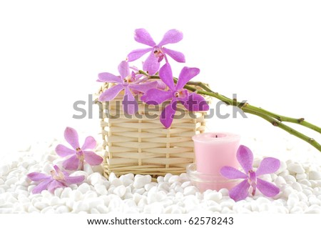 Spa still life with basket of pink orchid with candle on zen white pebble - stock photo