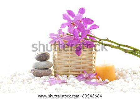 Spa still life with basket of pink orchid with stacked stones and candle on zen white pebble - stock photo