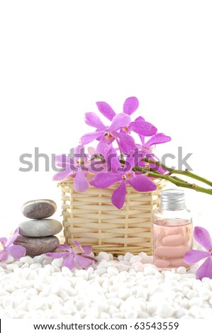 Spa still life with basket of pink orchid with stacked stones and massage oil on zen white pebble - stock photo