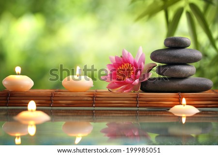 Spa still life with burning candles,zen stone and bamboo mat reflected in a serenity pool - stock photo