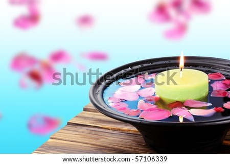 Spa  still life with candle and rose petals over bright background. - stock photo