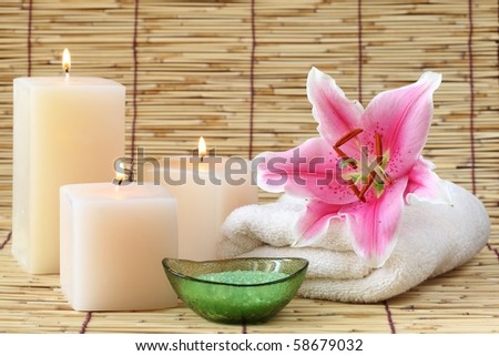 Spa still life with candles,bath-salt and towel on bamboo mat. - stock photo