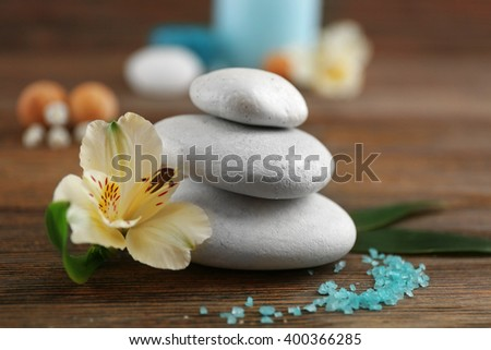 Spa still life with flowers and stones on wooden table closeup - stock photo